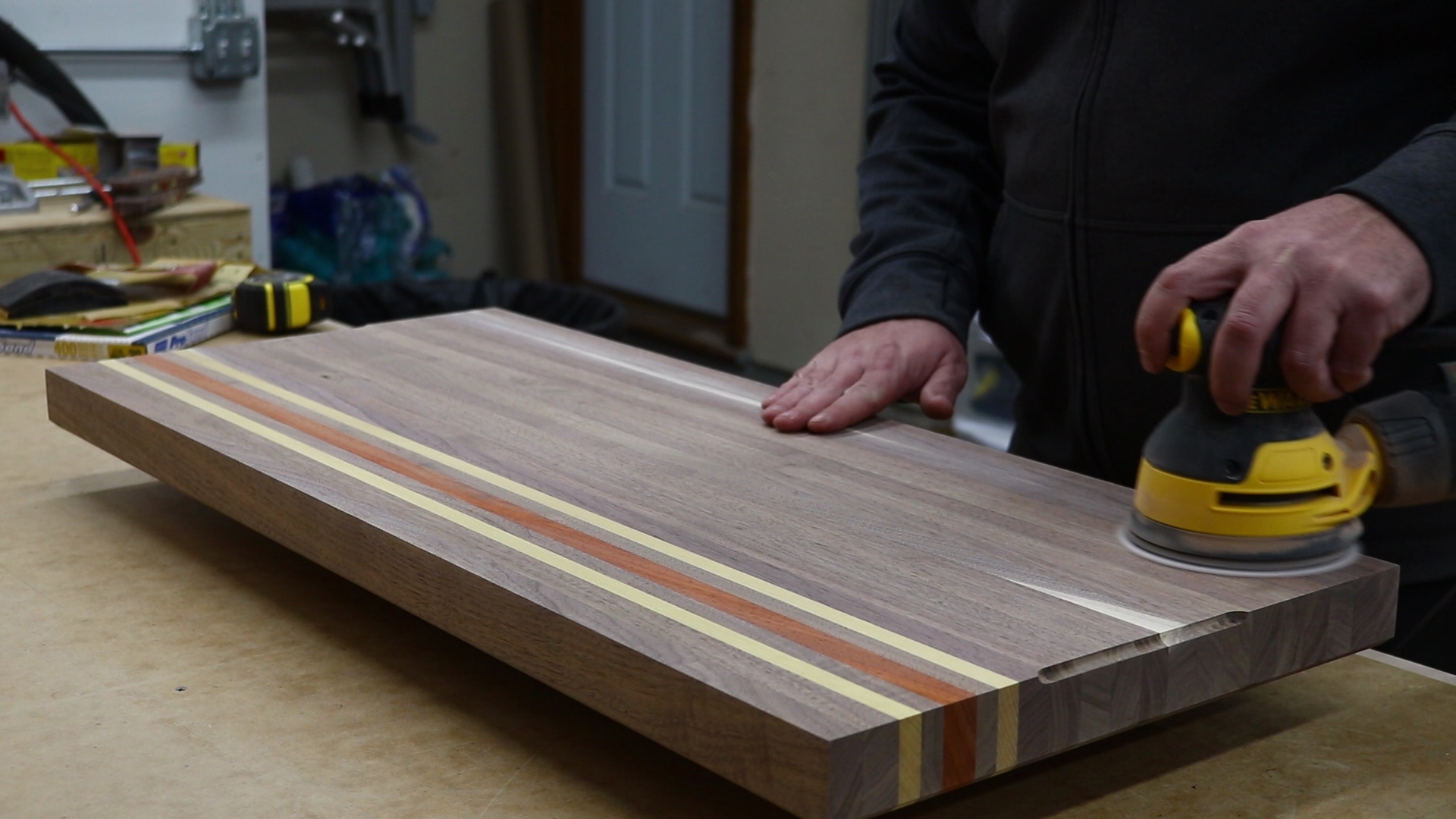 Lightly sanding the board to knock down any grain